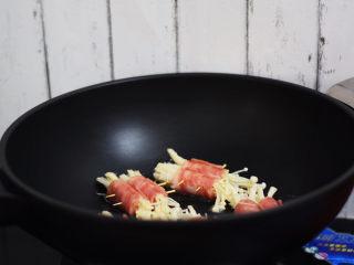 金针菇肥牛卷,放入培根金针菇卷,小火煎至培根变色收紧,翻面继续煎至培根变色收紧。每一边都要煎到。
