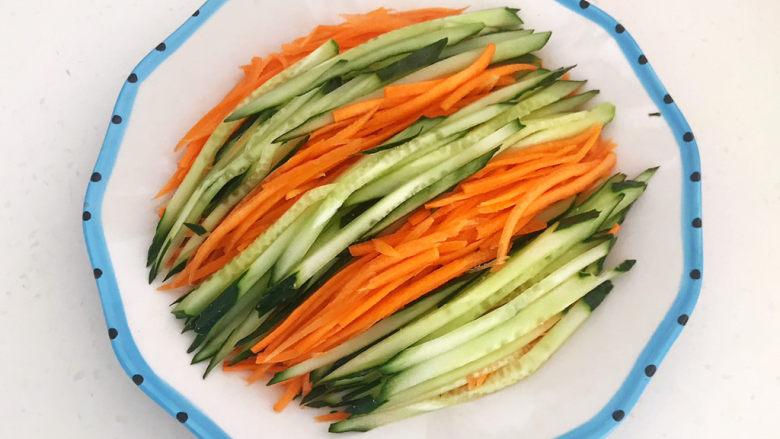 蒜泥黄瓜,把瓜丝和胡萝卜丝码入盘里