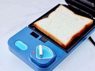鹌鹑蛋培根芝士三明治,烤盘里先放入一片吐司。