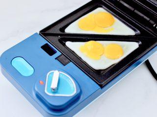 鹌鹑蛋培根芝士三明治,把鹌鹑蛋打散放入烤盘里。