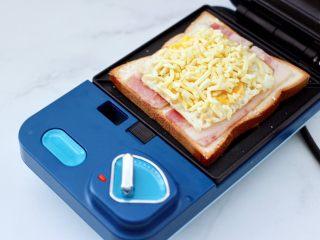 鹌鹑蛋培根芝士三明治,这个时候随自己喜好撒上芝士碎,喜欢多的就可以多放一些。