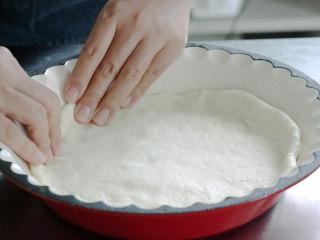培根火腿披萨,将面皮用手甩几下,甩均匀后放入烤盅