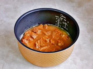 小米蒸排骨,再把煸炒过的排骨倒入电饭煲中,排骨铺平。