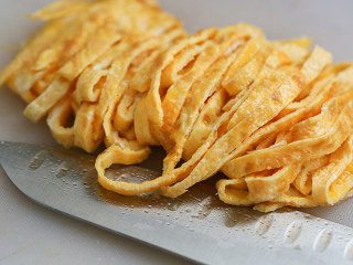 莴笋炒鸡蛋,把莴笋丝沥干水,把蛋饼切成丝;