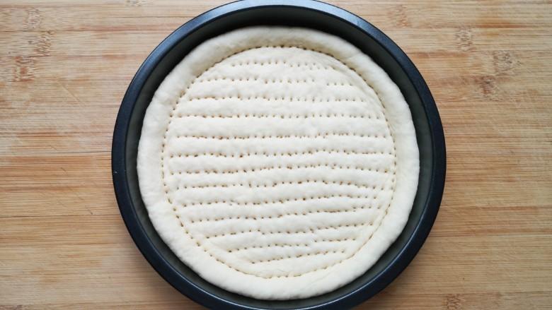 培根火腿披萨,用叉子扎满小孔,防止饼皮在烤制的过程中中间凸起。