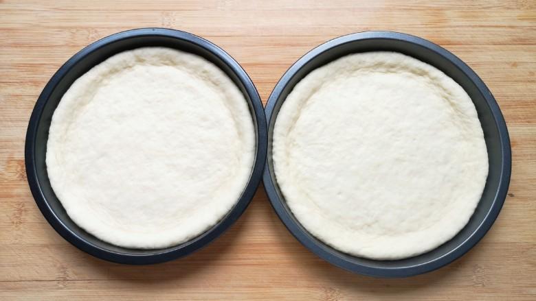 培根火腿披萨,发酵好的面团揉光排气,分成两份再次揉光,擀成和模具大小一致的面饼,放进披萨盘里。