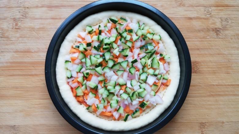 培根火腿披萨,撒上胡萝卜、黄瓜和洋葱小丁。