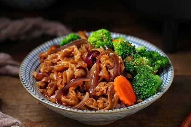 日式肥牛饭,将米饭盛入碗中,摆上西兰花和胡萝卜,上面铺肥牛再淋适量的汤汁。