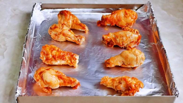 新奥尔良烤鸡腿,腌制好的鸡腿摆放在垫好锡纸的烤盘中。