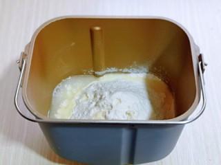 """香肠馒头卷,首先将称好的液体""""玉米油,牛奶""""先倒入面包桶中,再加入鸡蛋,糖,面粉,酵母粉。"""