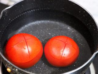 茄汁玉米鸡丁,番茄洗净底部切十字,放入开水中焯烫