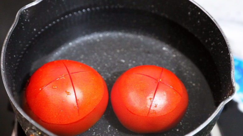 茄汁玉米鸡丁,<a style='color:red;display:inline-block;' href='/shicai/ 59'>番茄</a>洗净底部切十字,放入开<a style='color:red;display:inline-block;' href='/shicai/ 156925'>水</a>中焯烫