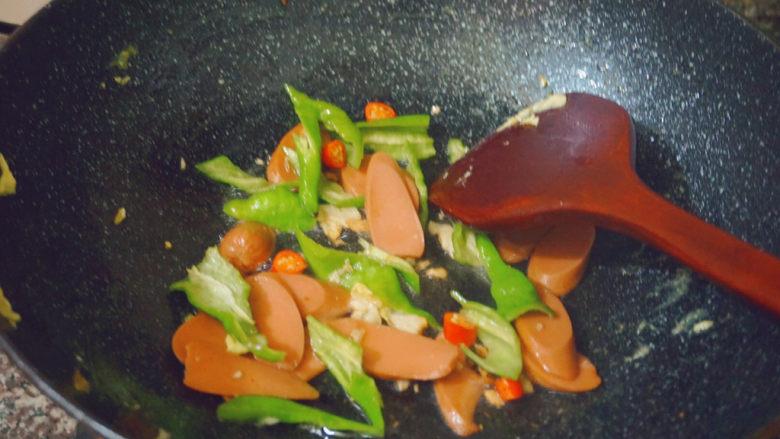 香肠炒蛋,倒入香肠和青椒大火翻炒3-4分钟