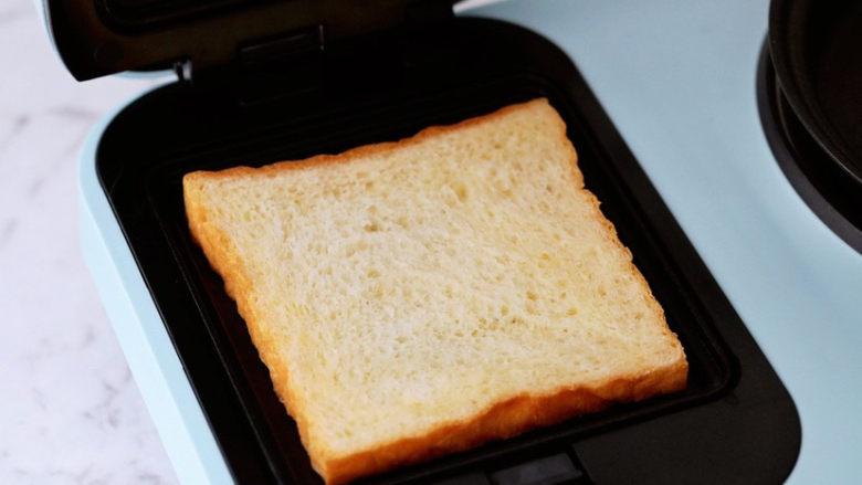 紫薯鸡蛋三明治,接着打开三明治机,将三明治烤盘装上,放入一片吐司片