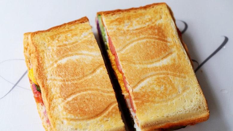 紫薯鸡蛋三明治,取出从中间切开,再搭配一杯牛奶和水果,一份营养美味的早餐就做好了