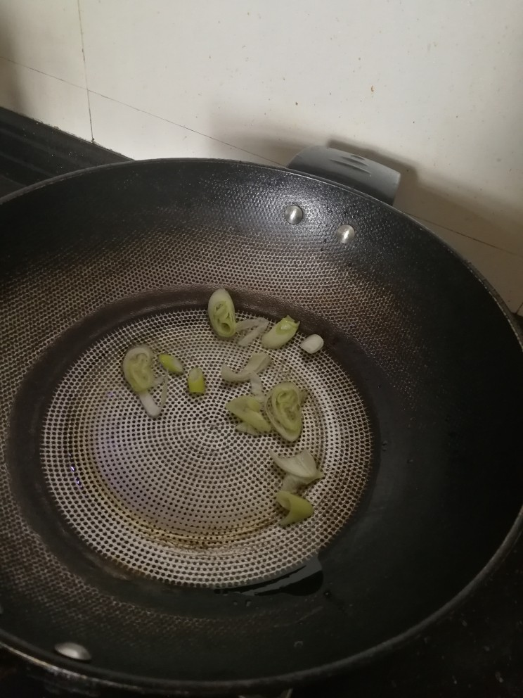 豌豆炒虾仁,加入葱花炝锅。