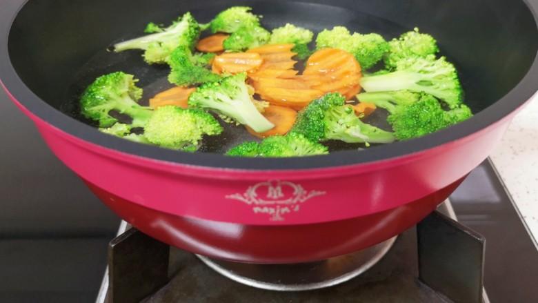 日式肥牛饭,锅里放水,加一点盐和食用油烧开,下入西蓝花和胡萝卜焯熟。