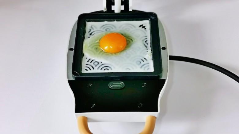 芝士火腿三明治,我们首先煎<a style='color:red;display:inline-block;' href='/shicai/ 9'>鸡蛋</a>,烤盘刷油,再磕入<a style='color:red;display:inline-block;' href='/shicai/ 9'>鸡蛋</a>,盖上盖子2分钟左右,取出,依次做好。