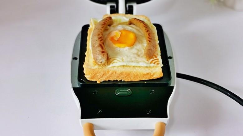 芝士火腿三明治,加入煎好的鸡蛋,脆皮肠放两边,如图。