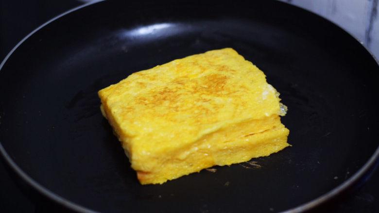 芝士火腿三明治,平底锅刷少许食用油烧热,把沾裹蛋液的吐司放入,小火煎至金黄色