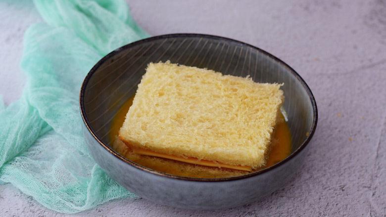 芝士火腿三明治,把夹好芝士火腿的吐司放入蛋液中