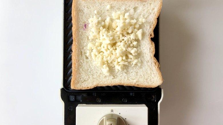 紫薯肉松芝士三明,三明治机里放一片<a style='color:red;display:inline-block;' href='/shicai/ 585'>吐司</a>,中间放上马苏里拉奶酪碎,用芝士片也可以。