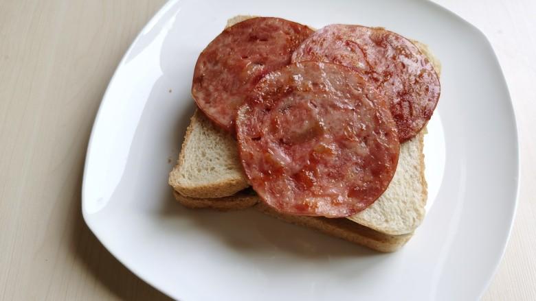 芝士火腿三明治,将火腿放到面包片上。