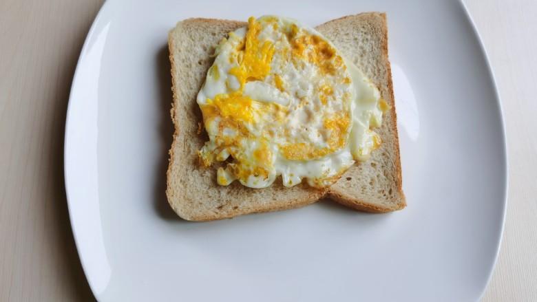 芝士火腿三明治,煎熟的鸡蛋放到面包片上。