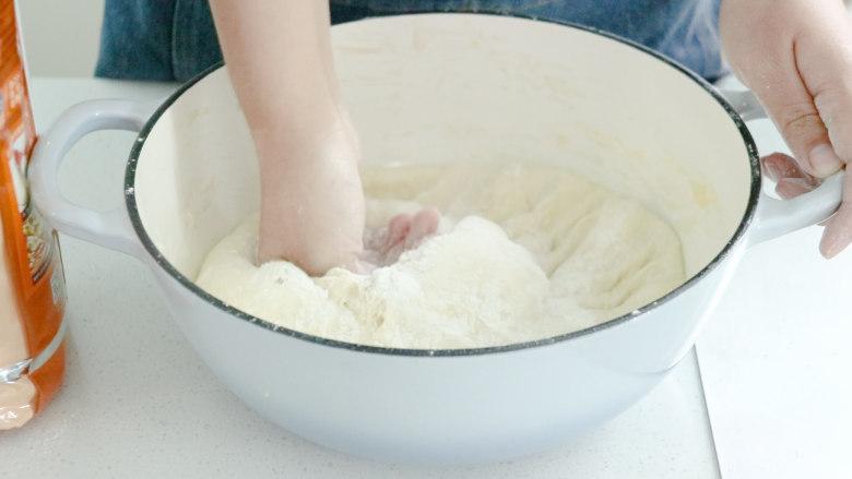 芝士火腿三明治,接下来给面团排气,撒上一些面粉,进行简单捶打,简单的将面揉1分钟就行。这个步骤主要就是给面团排气