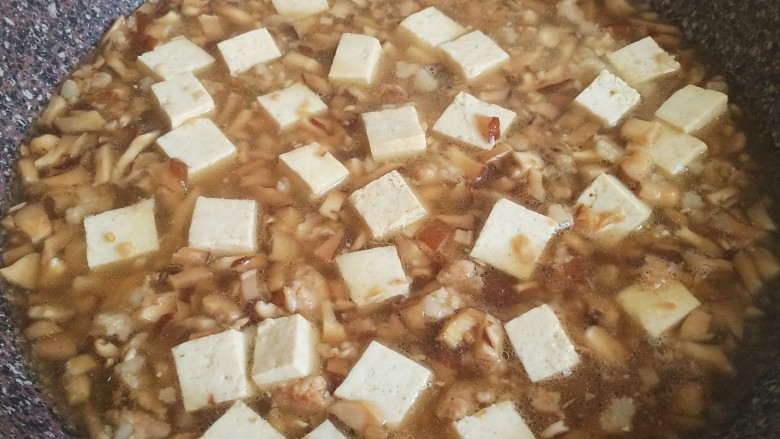 香菇肉末豆腐,倒入盐,清水和豆腐,开始炖