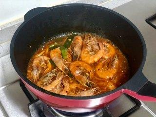 好吃到吮指的油焖大虾,加入一小碗水,水沸后放入煎好的大虾,炒匀。