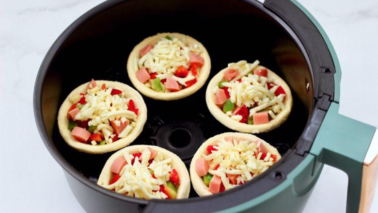 蛋挞火腿时蔬小披萨,空气炸锅提前200度预热5分钟后,把做好的蛋挞小披萨放入炸篮里。