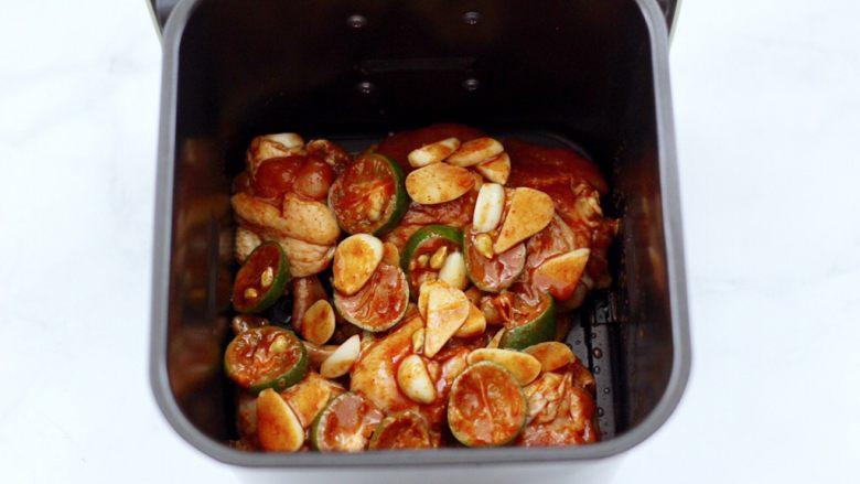 蒜香青柠鸡翅根,上面铺上大蒜片和青柠檬片。