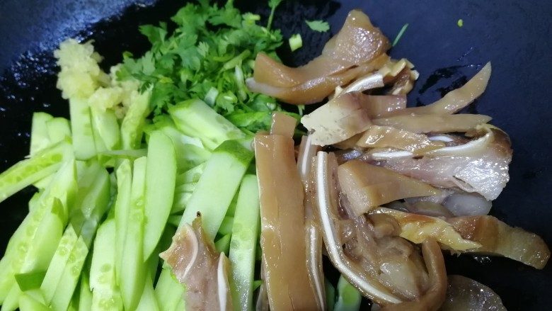 黄瓜拌猪耳朵,放入黄瓜条,切好的猪耳朵,香菜末,蒜末。