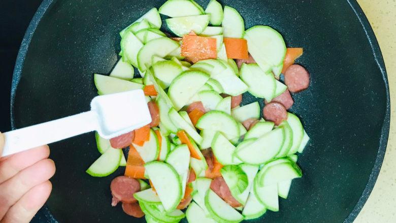 西葫芦炒火腿,炒至西葫芦片出水,撒上盐调味