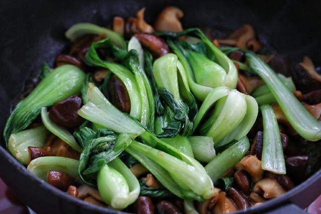 香菇炒青菜,把炒好的油菜倒入锅中与香菇混合翻炒均匀。