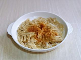 油炸金针菇,淋干水分,放入盘中,加入盐,十三香,抓拌均匀,腌制10分钟。