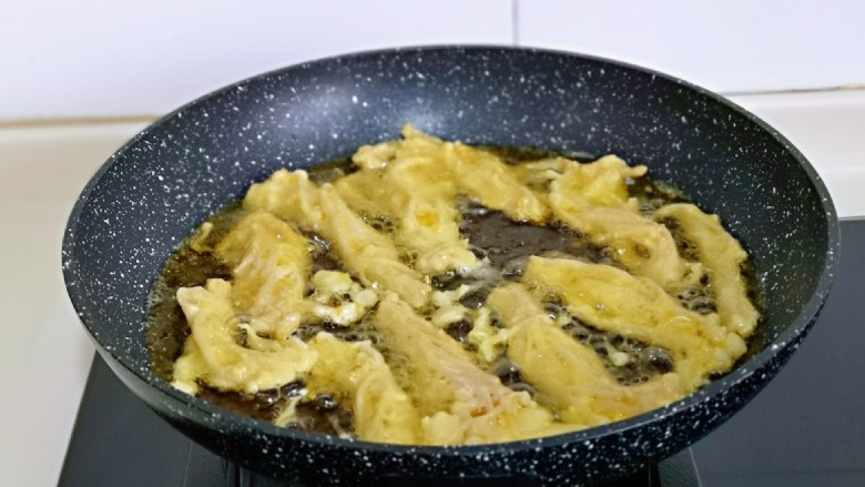 油炸金针菇,油温5成热左右时,用筷子夹入裹好面糊的金针菇,中小火炸,时间2分钟左右,炸好捞出,依次炸完。