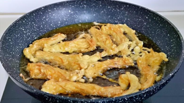 油炸金针菇,待油温再次生高时,进行复炸一次,时间不要过长,30秒左右立即捞出,口感更酥脆。