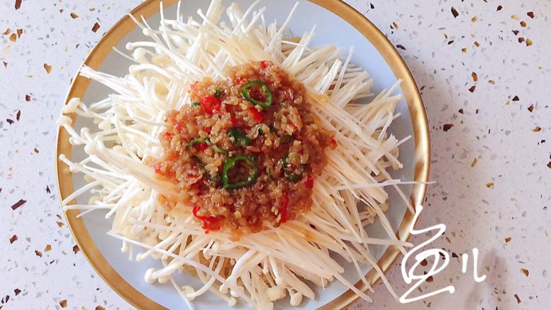 蒜蓉粉丝蒸金针菇,将蒜蓉辣椒碎摆放在金针菇上