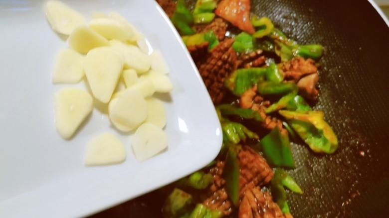 青椒炒猪腰,放入蒜片增香