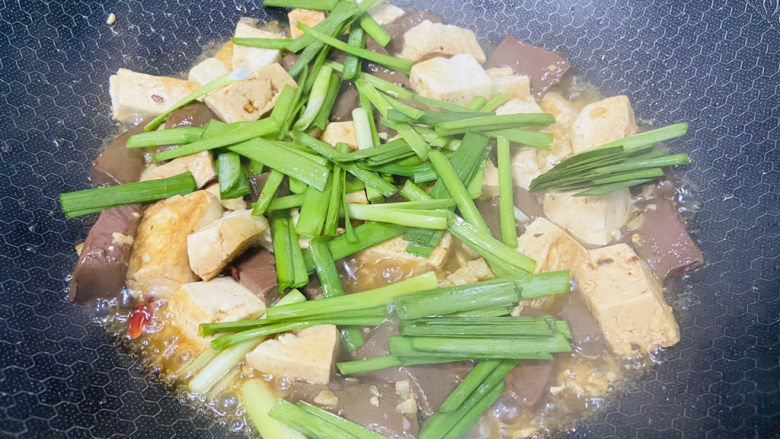 鸭血豆腐,放入韭菜焖煮断生即可