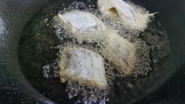椒盐带鱼,油锅油烧至五成热,放入带鱼炸至。
