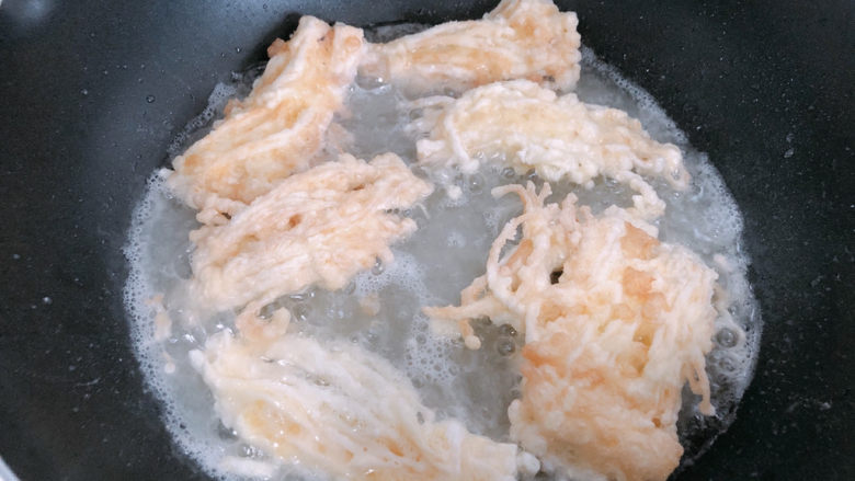 油炸金针菇,放入锅内油炸。
