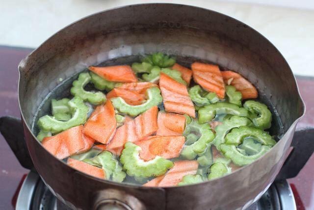 苦瓜炒虾仁,取一个小锅添适量清水烧开,放入苦瓜和胡萝卜焯烫约一分钟,捞出过凉水沥干水分备用。