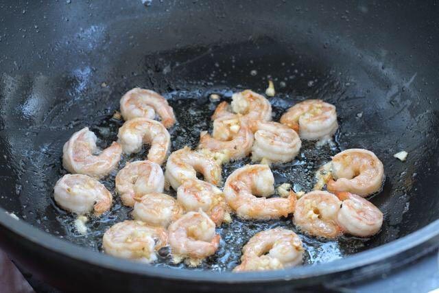 苦瓜炒虾仁,接着放入腌制好的虾仁,煎炒至两面变成红色。