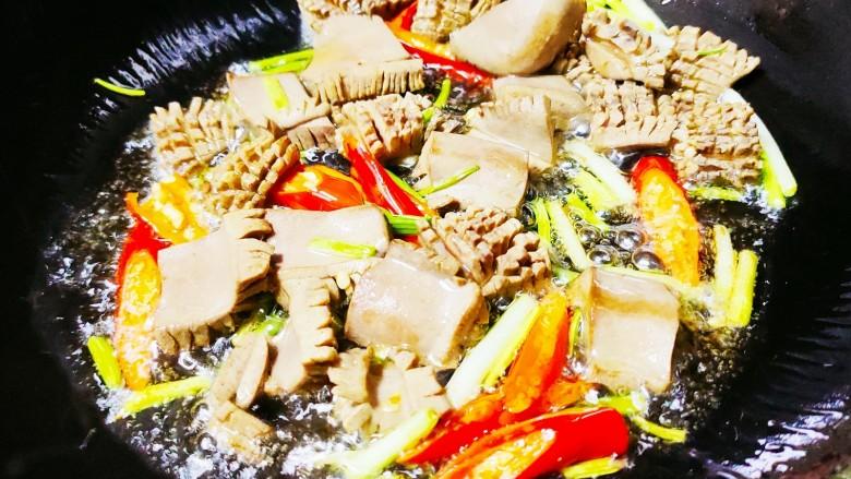 青椒炒猪腰,锅中倒油,油热后放入小米椒,葱根,再倒入腰花