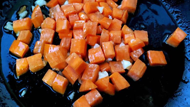 毛豆炒鸡丁,另起锅倒入底油加热放入蒜粒爆香放入胡萝卜炒至断生