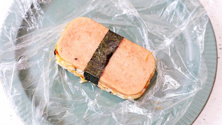 午餐肉饭团,最后将保鲜膜提出,取出饭团,再包上一条海苔即可