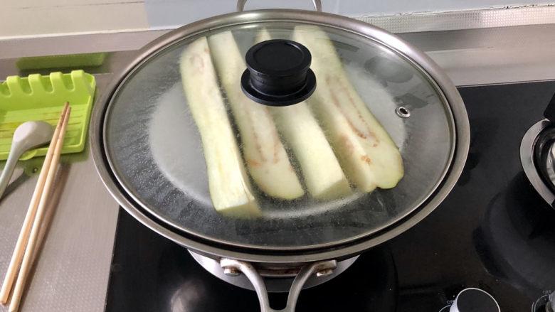 蒜蓉茄子,蒸锅烧水,放入茄子,水开蒸10到15分钟,到筷子可以轻松戳进茄子,即可关火